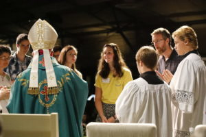 Bishop Jeffrey Monforton receiving the gifts at mass at Catholic Familyland