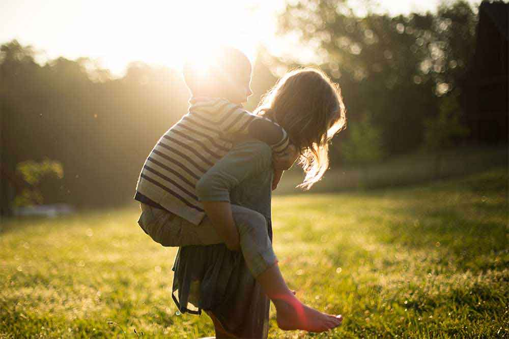 A young girl giving a piggyback ride to her barefoot younger brother outside in the grass as the sun begins to set