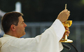 Fr. Klem elevating Jesus in the most Holy Eucharist at mass